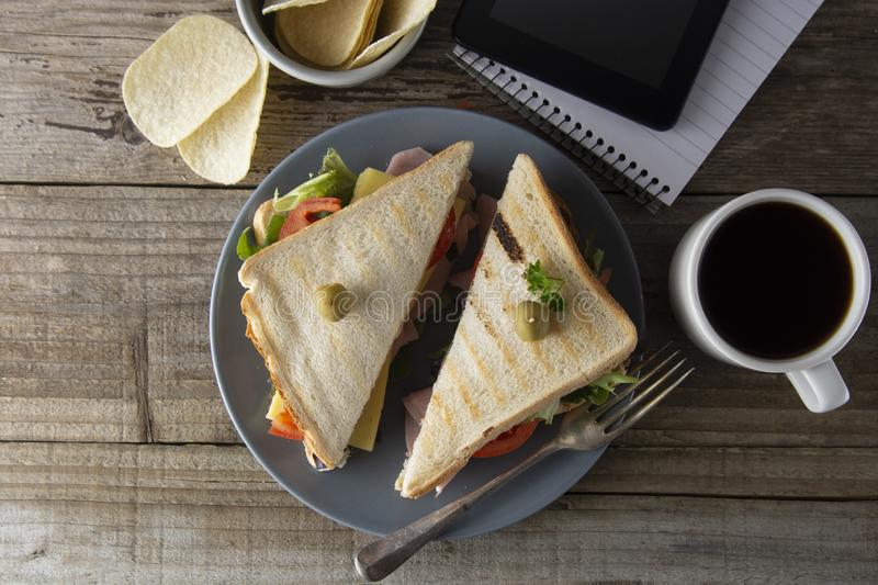 Unhealthy eatting at work place. Triangle, club sandwich with ham and vegetables. Tablet, gadget screen and notebook. Cup of royalty free stock image