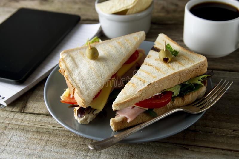 Unhealthy eatting at work place. Triangle, club sandwich with ham and vegetables. Tablet, gadget screen and notebook. Cup of royalty free stock images