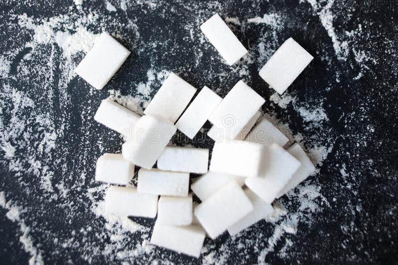 Unhealthy food concept - sugar and flour on a black background. royalty free stock image