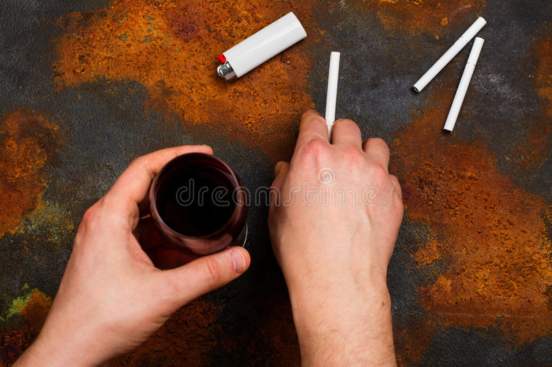 Unhealthy habits concept. Man holding cigarette and glass of red wine in his hands. Bad unhealthy habits or new year resolution concept. Copy space royalty free stock photos