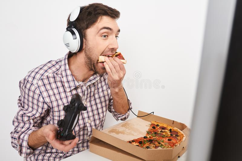 Unhealthy lifestyle. Close up of young beautiful funny bearded man with dark short hair playing online games with stock photo