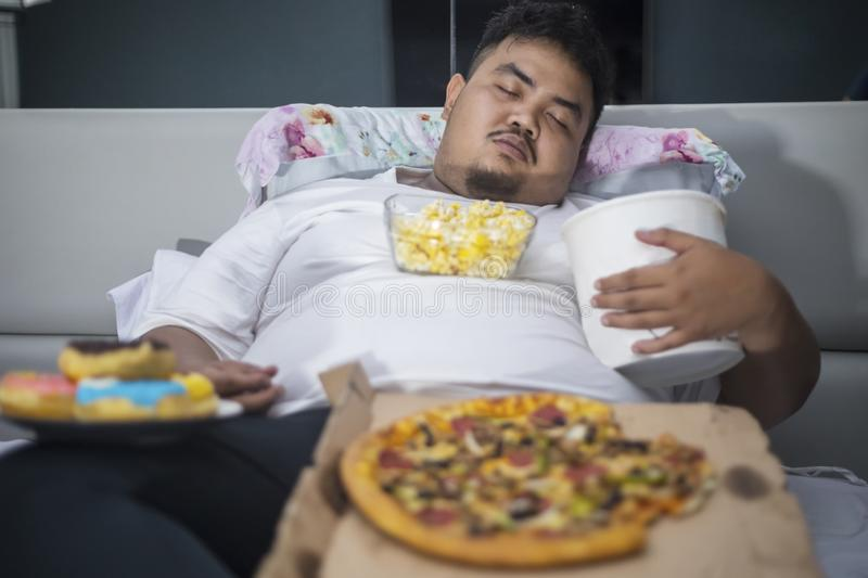 Asian obese man sleeping with junk foods. Unhealthy lifestyle concept: Asian obese man eating junk foods during sleeping on the bed stock photography