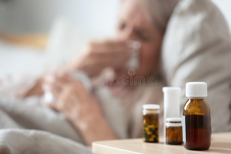 Unhealthy mature woman suffering from cold, meds on bedside table royalty free stock photography