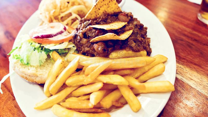 Unhealthy meal with mexican nacho chips loaded with beef, cheese, fries, onion rings. And hot souse stock photo