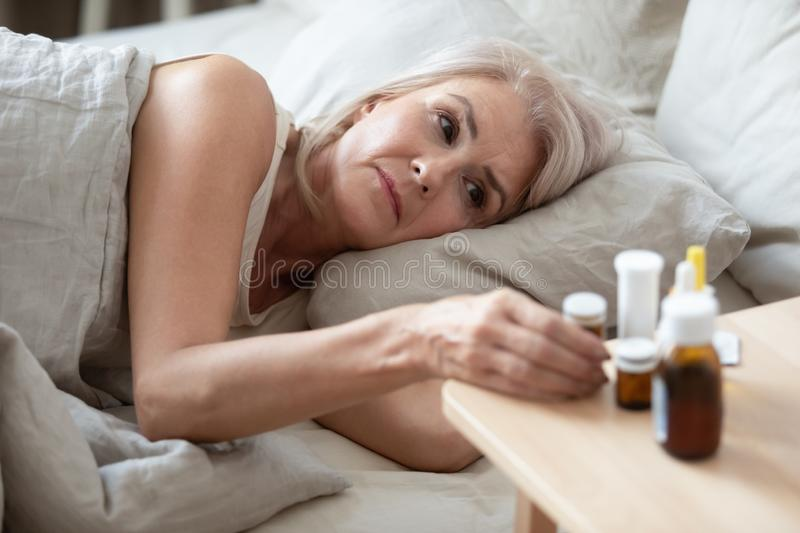Unhealthy older woman taking pills from bedside table close up. Unhappy mature female lying in bed, taking medicine from cold or insomnia, suffering from flu stock photography