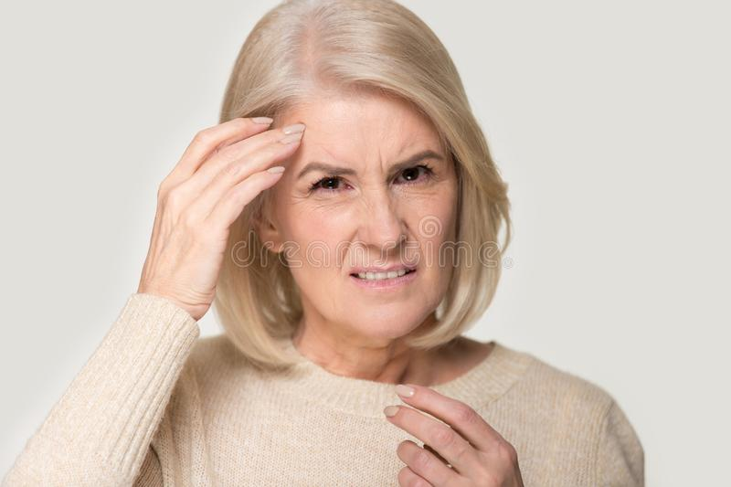 Unhealthy senior woman isolated on studio background having migraine royalty free stock images