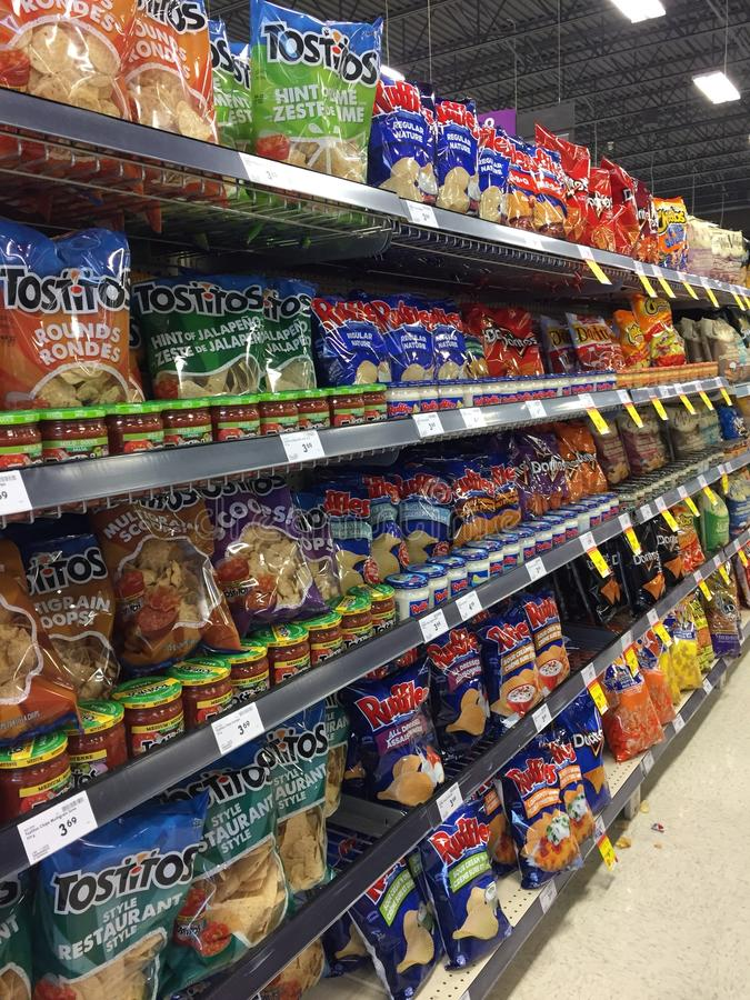 Unhealthy snack isle displaying chips and other snacks at grocery store stock photos