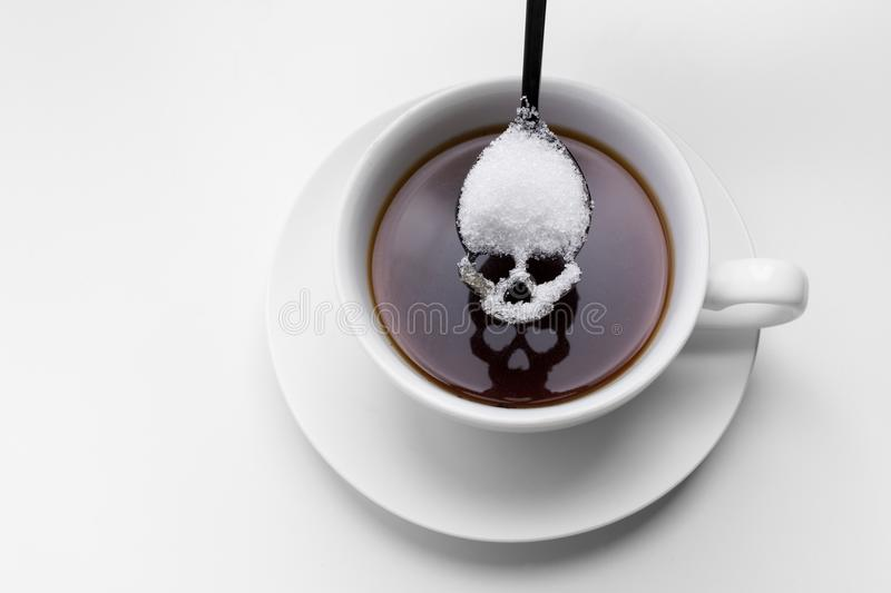 Unhealthy white sugar concept. Scull spoon with sugar and cup of black coffee stock photos