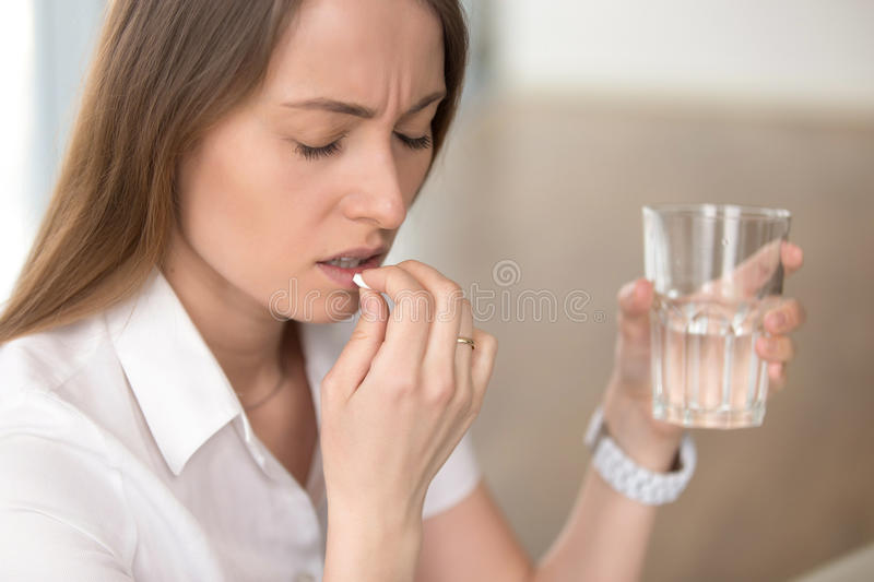 Unhealthy woman feeling migraine headache, taking pill medicatio. Unhealthy woman with pained facial expression feels unwell, suffering from migraine headache royalty free stock images