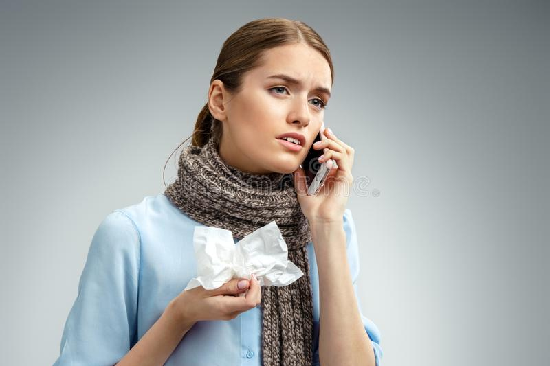 Unhealthy woman with flu calling on the phone. Photo of american woman in blue shirt suffering cold and winter flu virus on gray background. Medical concept stock photo