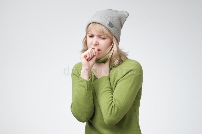 Unhealthy young blonde woman coughing a lot, suffering with cough, has a chest pain. Unhealthy young blonde woman coughing a lot, suffering from chest pain royalty free stock photos