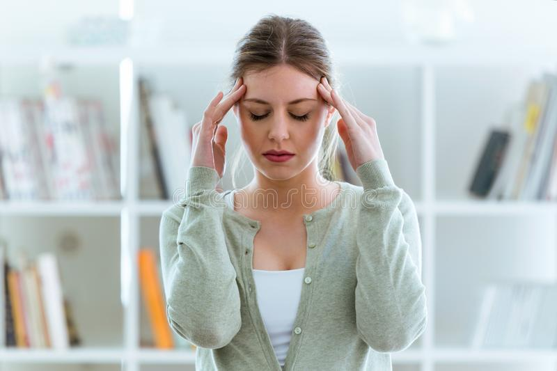 Unhealthy young woman with headache touching his head at home. royalty free stock image