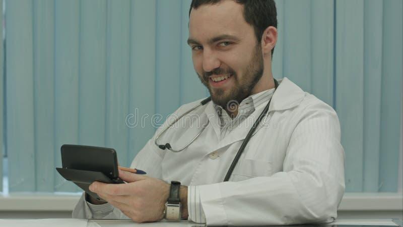 Unheimlicher bärtiger Doktor mit einem Taschenrechner Berechnung des Preises stockbilder