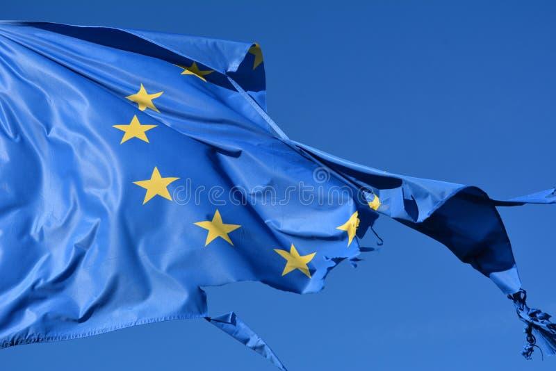 A União Europeia doze star a bandeira rasgada e connosco no vento no céu azul foto de stock royalty free