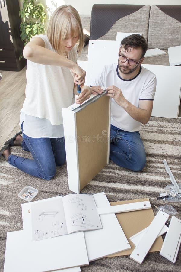 A união gerencie a mobília para o auto-conjunto A mulher está parafusando a asseguração de parafuso o trilho da gaveta com uma ch imagem de stock