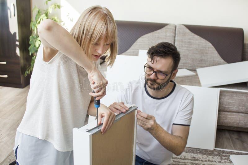 A união gerencie a mobília para o auto-conjunto A mulher está parafusando a asseguração de parafuso o trilho da gaveta com uma ch imagens de stock royalty free
