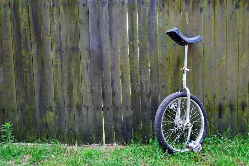 Unibike-monocycle Stellung gegen Bretterzaunhintergrund stockfoto