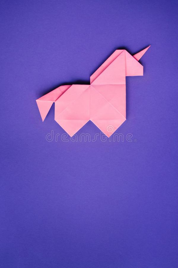 Unicórnio cor-de-rosa do origâmi no fundo ultravioleta foto de stock