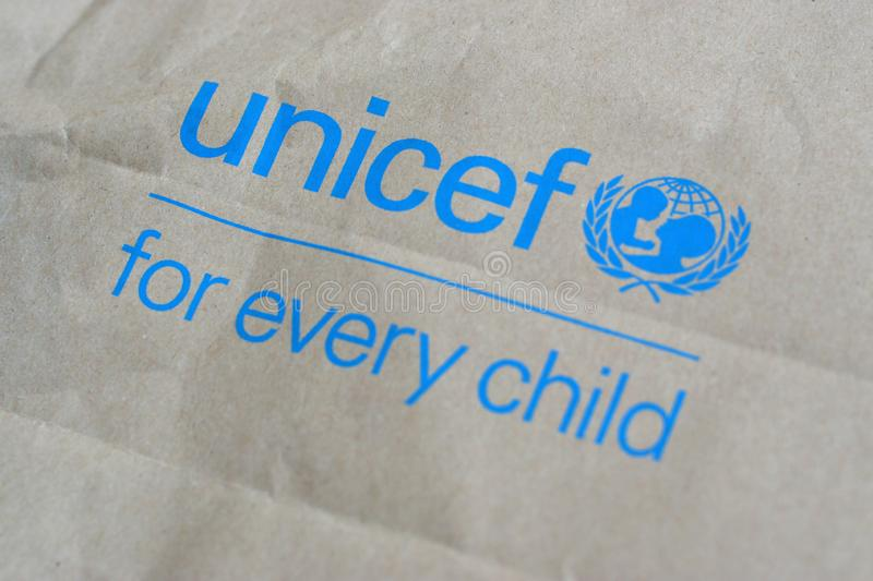 Unicef blue logo on brown paper bag, United Nations Childrens Fund is agency responsible for providing humanitarian and. NY, USA - DECEMBER 29, 2019: Unicef blue royalty free stock photo