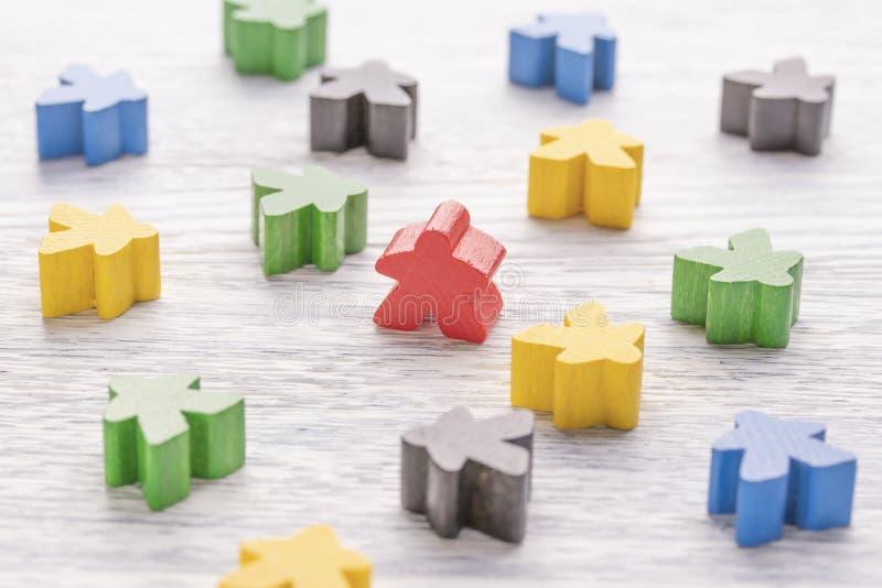 Unicidade, individualidade e diferença Figura de madeira vermelha em uma multidão de cor diferente foto de stock
