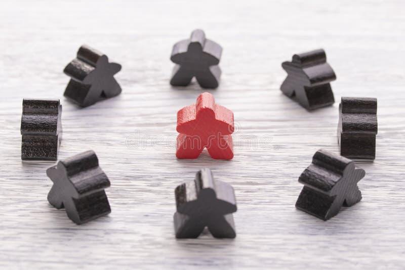 Unicité, individualité et différence Figure en bois rouge dans une foule de couleur différente images stock