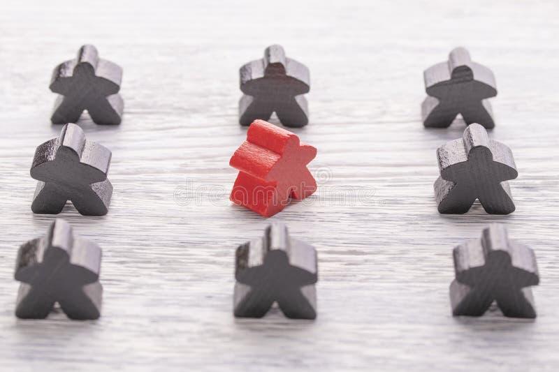 Unicité, individualité et différence Figure en bois rouge dans une foule de couleur différente photo libre de droits