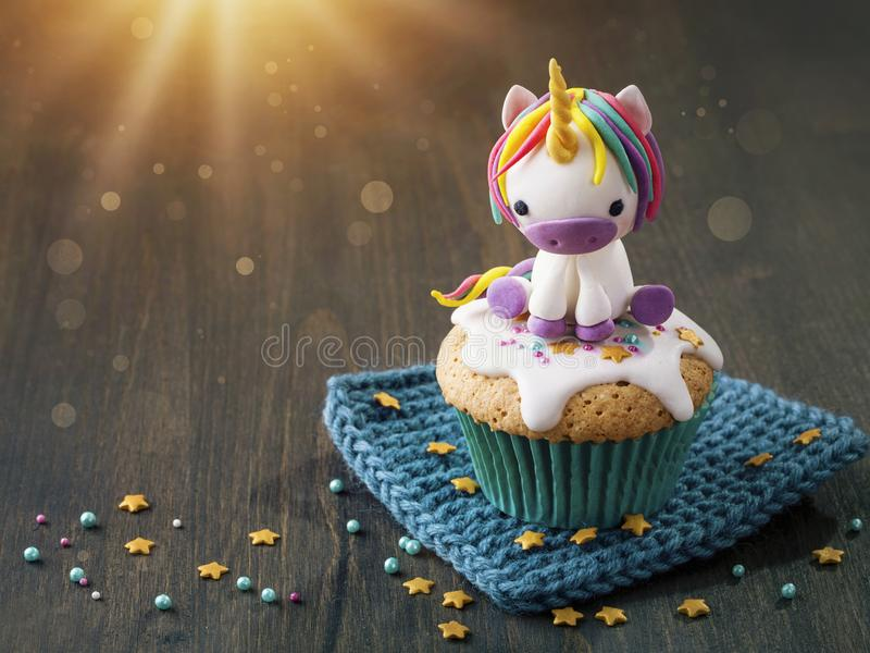 Unicorn cupcake for a party. Unicorn cupcake on a brown wooden background stock photo
