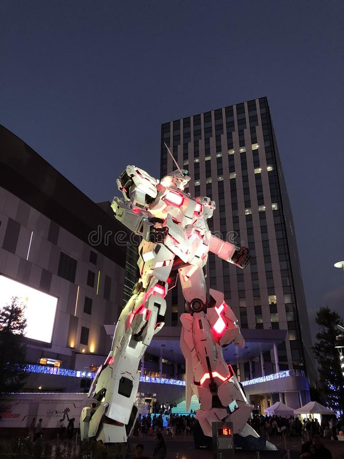 Unicorn Gundam se tenant devant le plongeur City Tokyo Plaza à la ville d'Odaiba la nuit images libres de droits