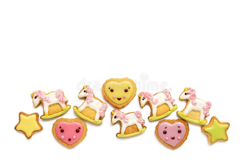 Unicorn and heart shaped sugar cookies decorated with pastel royal icing on white background stock photography