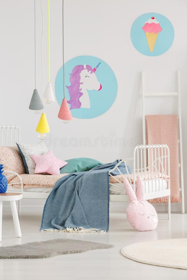 Unicorn and ice-cream posters on the wall and lamps above a bed royalty free stock photo