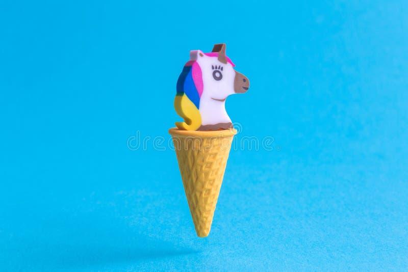 Unicornio en el extracto del cono de helado aislado en azul foto de archivo libre de regalías