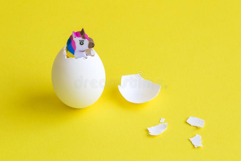 Unicornio que trama del huevo contra el concepto creativo mínimo de pascua del fondo amarillo imagen de archivo