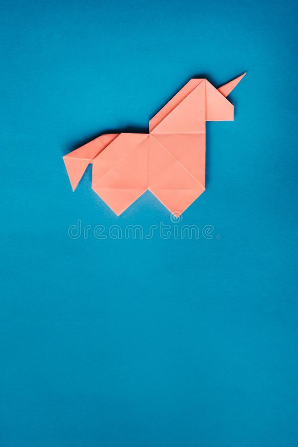 Unicornio rosado de la papiroflexia en fondo azul imagenes de archivo