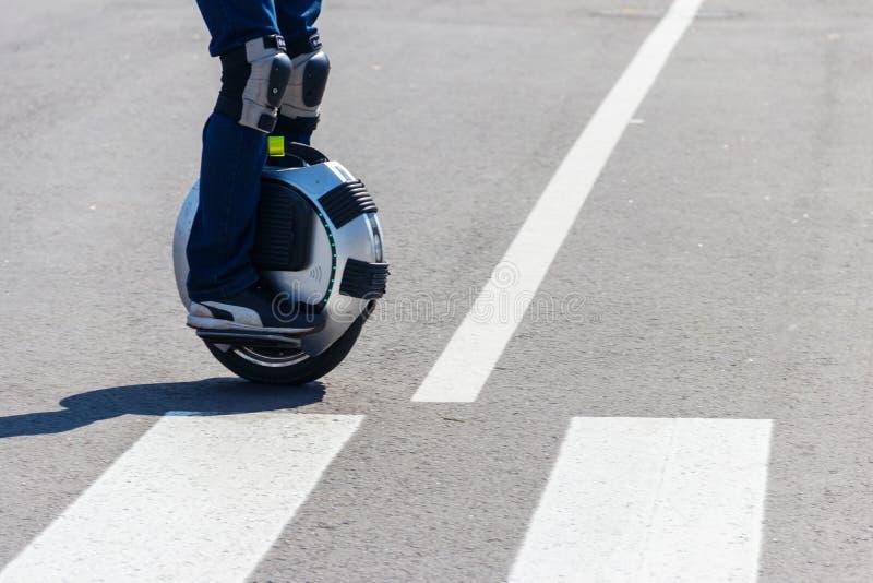 Unicycle bonde Passeios do homem na mono roda no cruzamento de zebra fotos de stock