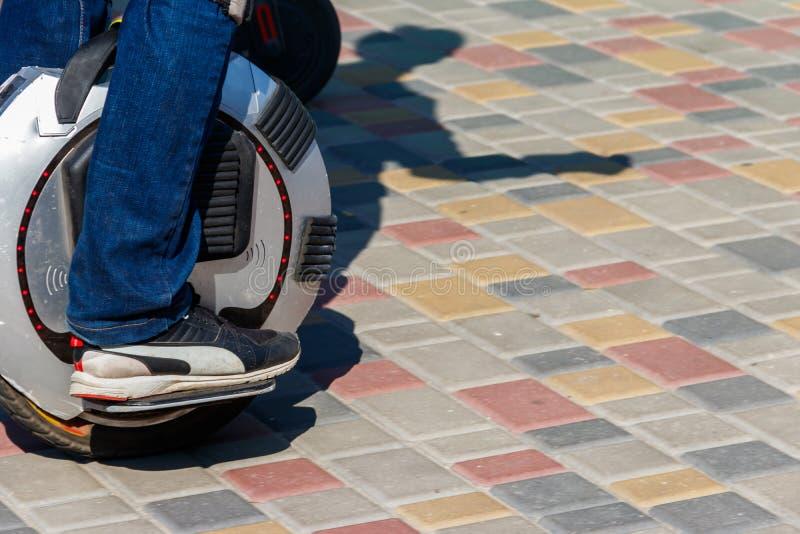 Unicycle eléctrico Paseos del hombre en mono de la rueda parque adentro imagenes de archivo