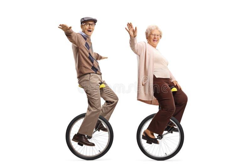Unicycles de montada idosos do homem e da mulher e sorriso na câmera imagens de stock