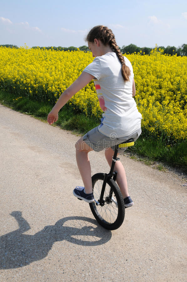 Unicyclist. Sportive teenager girl riding a unicycle stock photography