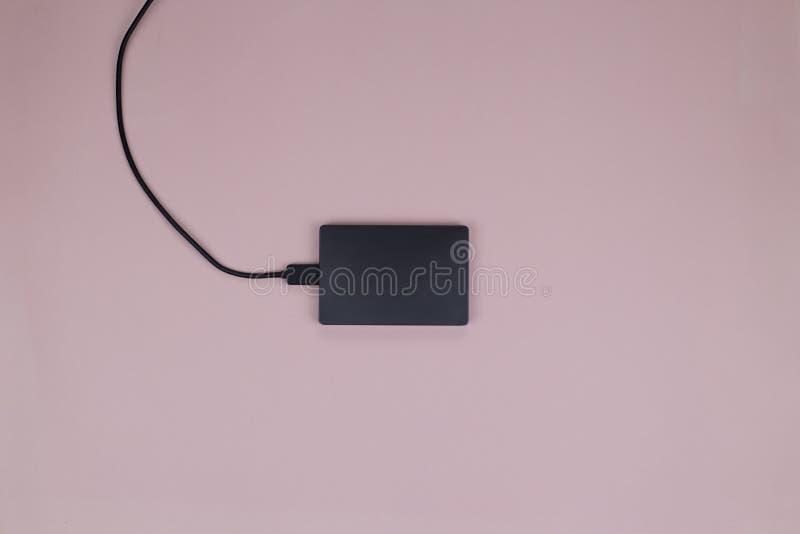 Unidad de disco duro externa negra moderna con un cable negro para conectar con un ordenador fotografía de archivo