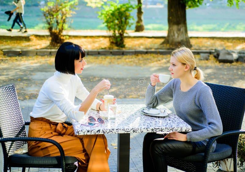 Unidad y amistad femenina Estrechas relaciones amistosas de la amistad verdadera Confíela en Los amigos de muchachas beben el caf imagenes de archivo
