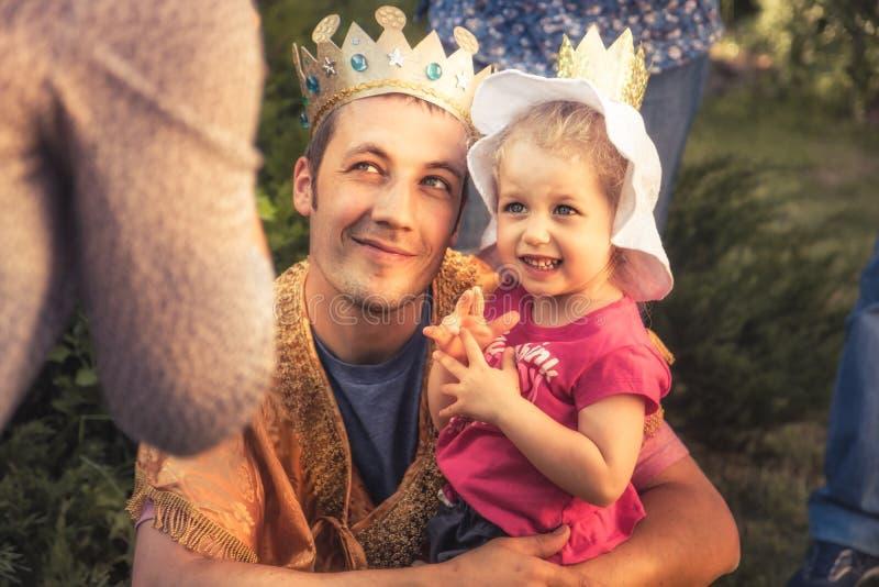 Unidad y parenting felices del concepto de la princesa de la hija del niño de la tenencia del padre del rey al aire libre foto de archivo libre de regalías