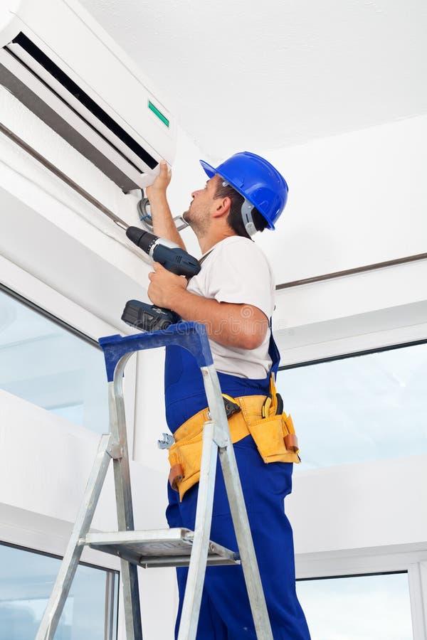 Unidade de condicionamento de ar da montagem do trabalhador fotografia de stock royalty free