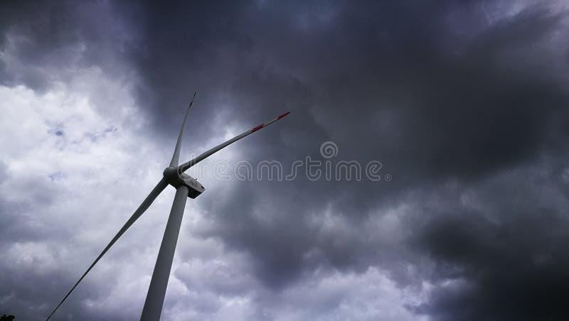 Unidade de energias eólicas que está apenas com cerco glommy das nuvens de chuva foto de stock