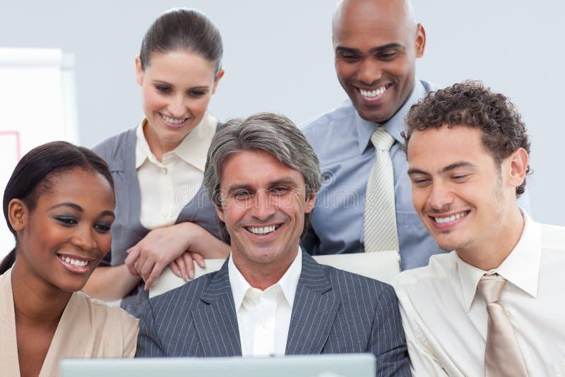 Unidade de negócio Multi-ethnic de sorriso que usa um portátil foto de stock