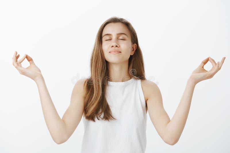 Unidade do sentimento com o universo através da meditação Jovem mulher feliz calma no equipamento na moda, olhos de fechamento e  fotografia de stock