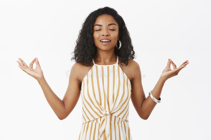 Unidade do sentimento com o universo durante todo a meditação Modelo fêmea de pele escura encantador calmo calmo no amarelo listr foto de stock