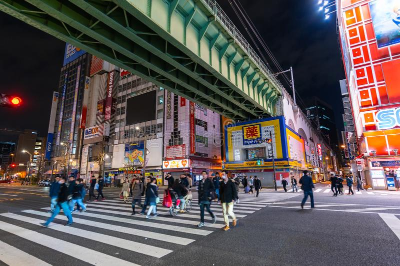 Unidendified people walk across the street in Akihabara at night, Tokyo, Japan. Akihabara, JAPAN - March 25, 2019: unidendified people walk across the street in royalty free stock photos