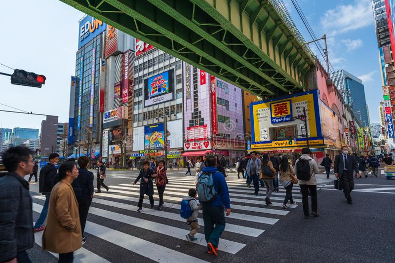 Unidendified people walk across the street in Akihabara at Tokyo, Japan. Akihabara, JAPAN - March 25, 2019: unidendified people walk across the street in royalty free stock images