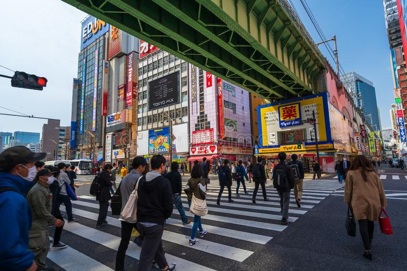 Unidendified people walk across the street in Akihabara at Tokyo, Japan. Akihabara, JAPAN - March 25, 2019: unidendified people walk across the street in royalty free stock photos