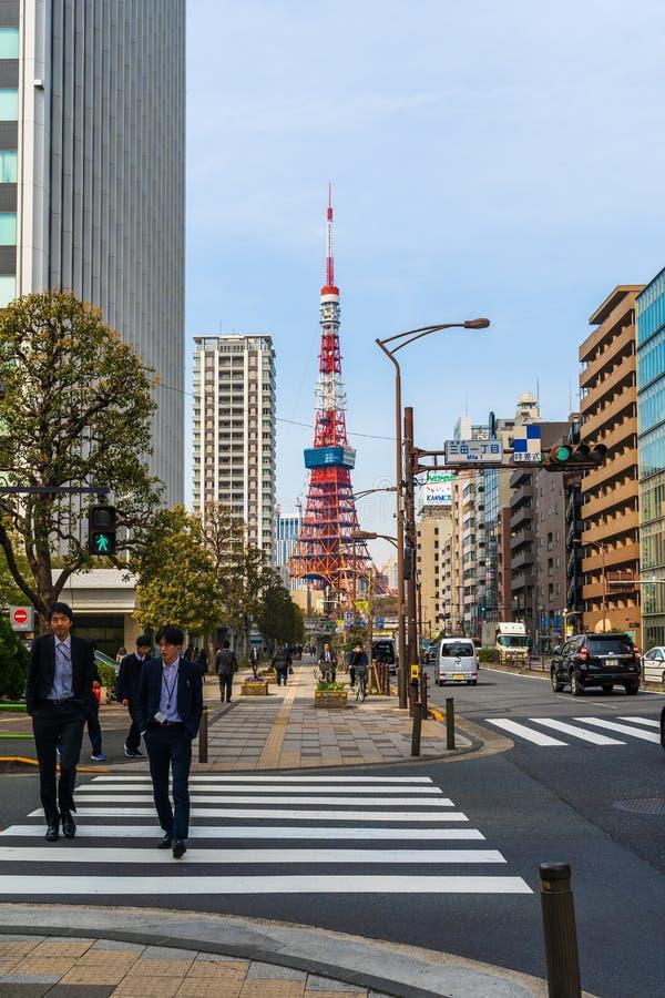 Unidendified people walk across the street in Tokyo city, Japan. TOKYO, JAPAN - March 25, 2019: Unidendified people walk across the street in Tokyo city, Japan stock photo