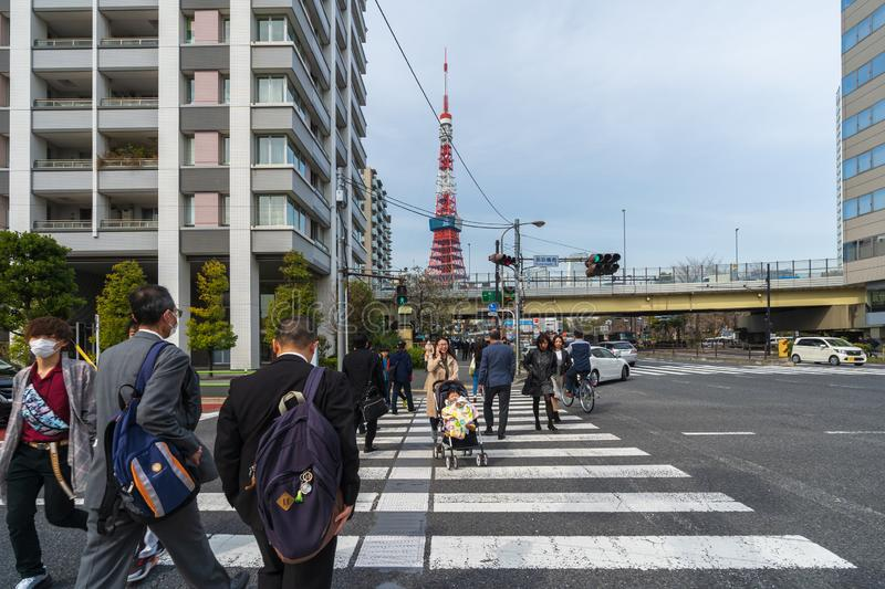 Unidendified people walk across the street in Tokyo city, Japan. TOKYO, JAPAN - March 25, 2019: Unidendified people walk across the street in Tokyo city, Japan royalty free stock image